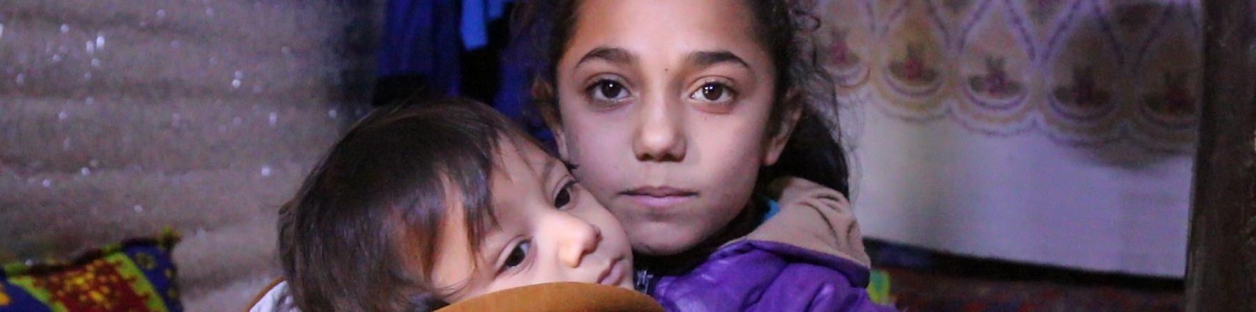bambina con cappotto viola tiene in braccio un bambino