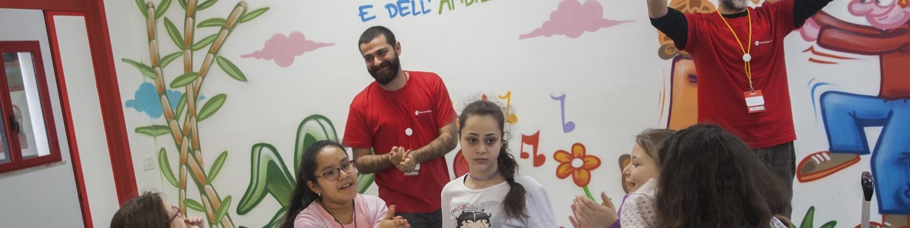 Bambini e operatori Save the Children intorno a un tavolo