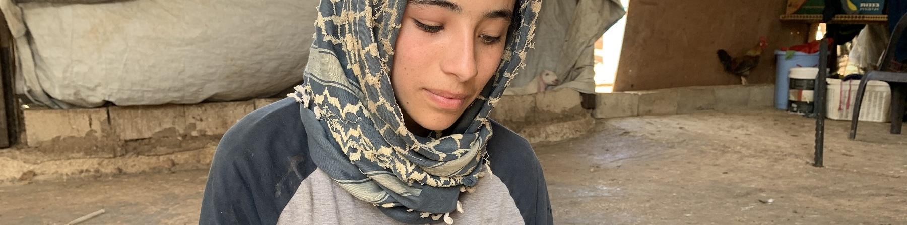 Ragazza palestinese con kufia in testa è seduta a terra e legge un quaderno che tiene poggiato sulle ginocchia