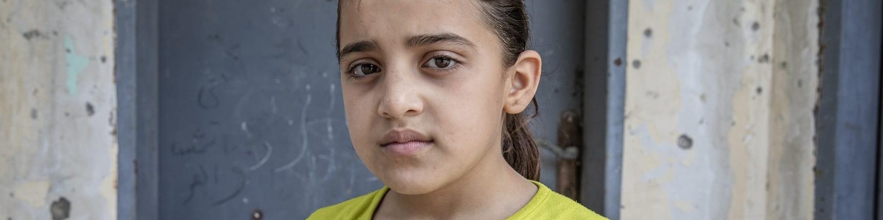 Mezzo busto di una bambina palestinese che indossa una maglietta gialla a maniche corte con alcune scritte colorate sopra. La bambina è castana ed ha i capelli raccolti in una coda.