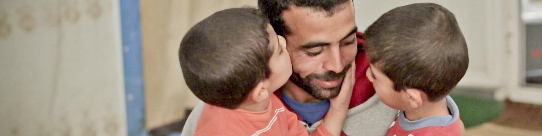 un papà chino sui figli, li abbraccia e uno dei due bambini gli accarezza la guancia e si avvicina per dargli un bacio