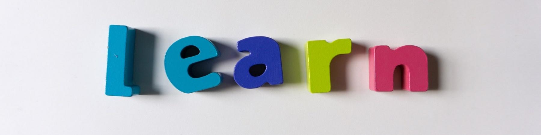 lavagnetta magnetica con attaccate lettere colorate a formare la parola learn