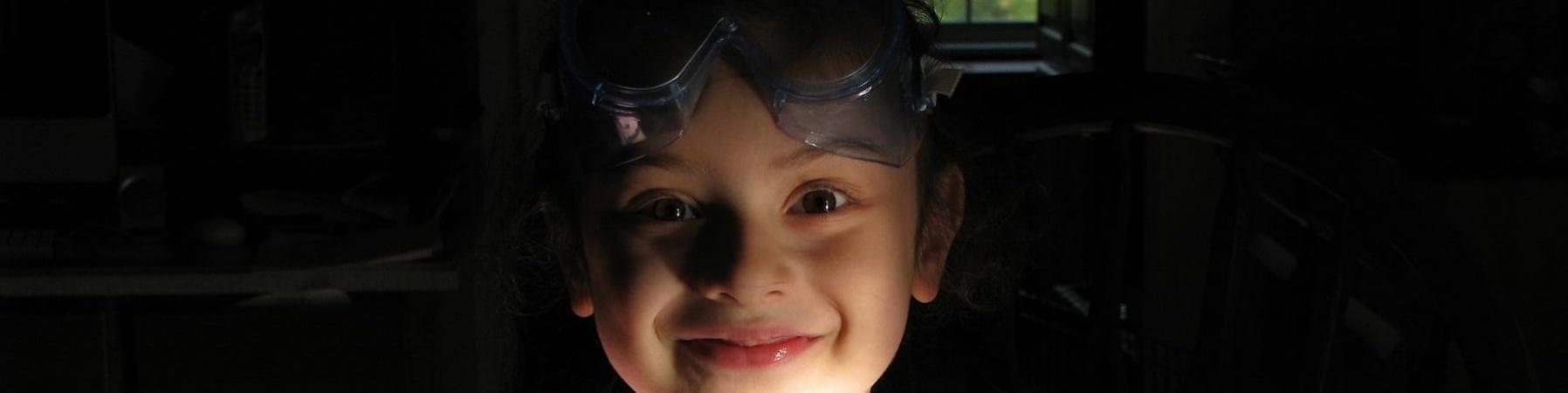 bambina sorridente con maschera snorkeling sulla fronte seduta al tavolo tiene in mano un pennello mentre lavora a un esperimento