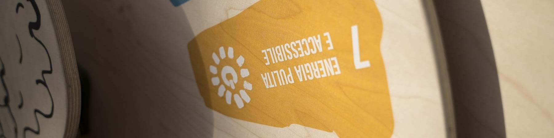 """Una ruota di legno appesa a un muro mostra in blocchi colorati gli obiettivi di sviluppo sostenibile. Nella foto viene inquadrato prevalentemente il goal """"energia pulita e accessibile"""" su sfondo giallo"""