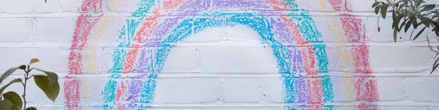 arcobaleno fatto con gessetti colorati su muro bianco