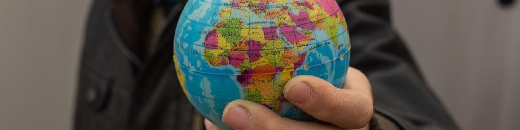 bambino tiene in mano un piccolo mappamondo
