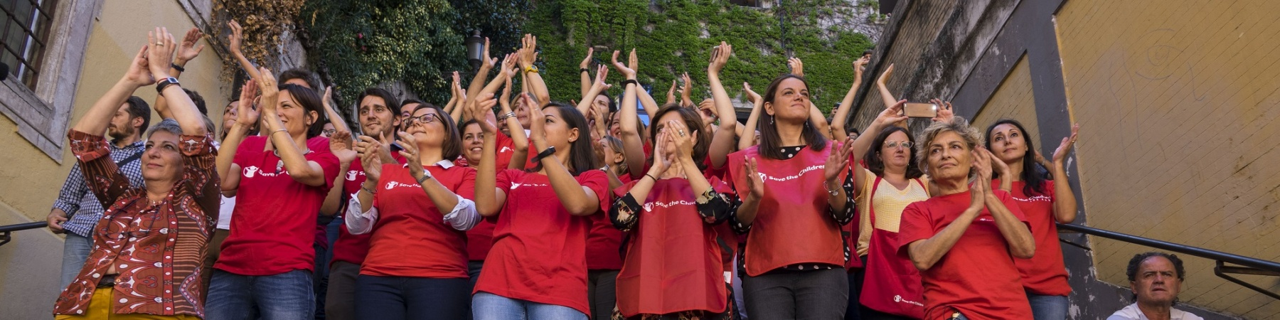 staff di save the children Italia applaude ai ragazzi che manifestano per il Global Strike fo Future, insieme a loro 4 bambini che applaudono sorridenti.