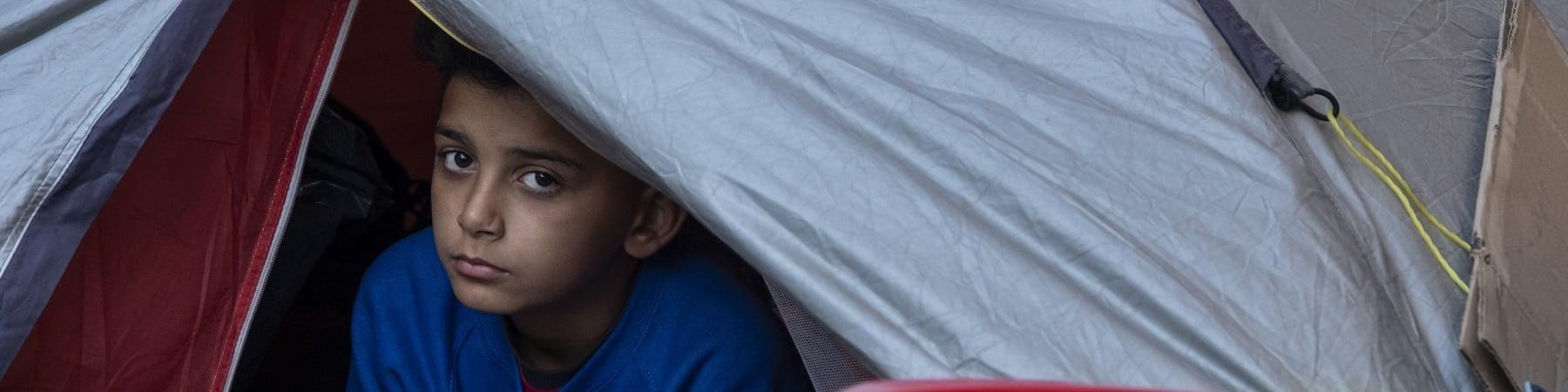 bambino si affaccia fuori a una tenda da campeggio in un campo profughi greco