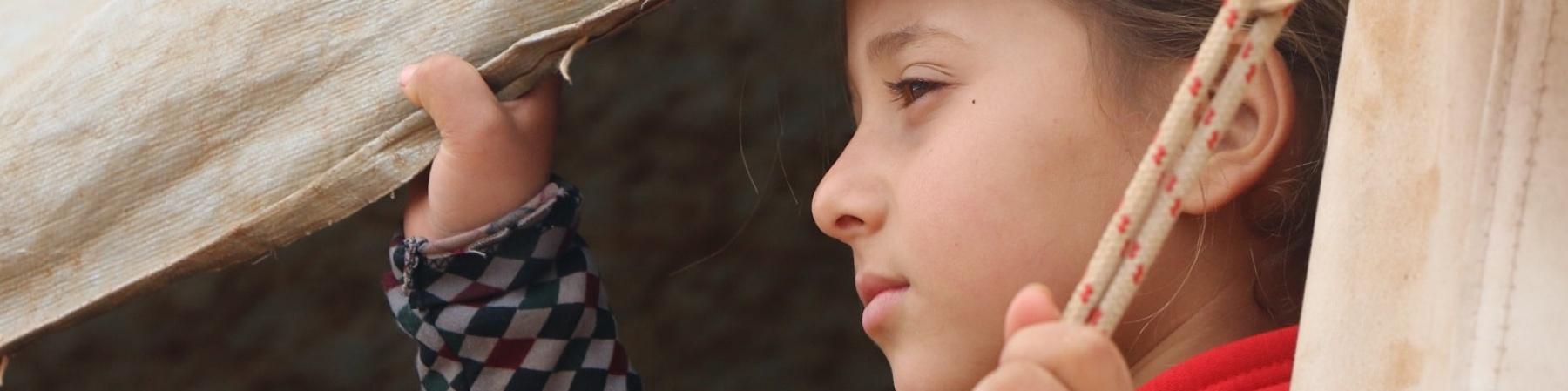 bambina siriana guarda verso sinistra attraverso una tenda che tiene aperta con una mano