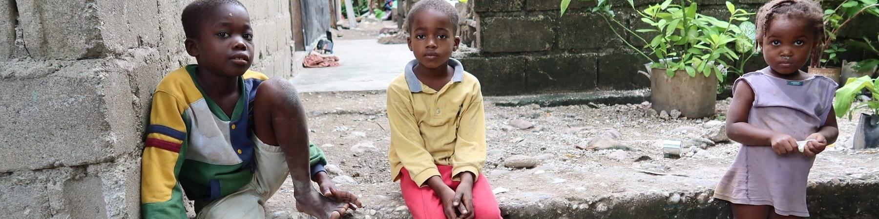 Tre bambini haitiani seduti su un gradino guardano in camera