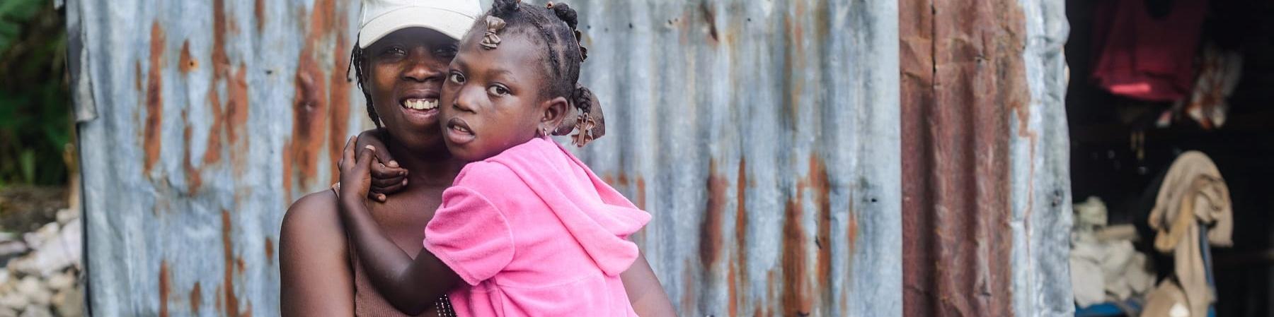Una donna haitiana tiene in braccio la sua bambina che indossa un vestito rosa e le tiene le braccia strette intorno al collo. La donna indossa una maglietta marrone e un cappellino bianco in testa. Dietro di loro si vedono le lamiere di una baracca.