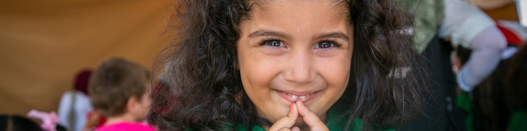 Foto mezzo busto bambina riccia con fiocco azzurro in testa e con le mani giunte davanti alla bocca