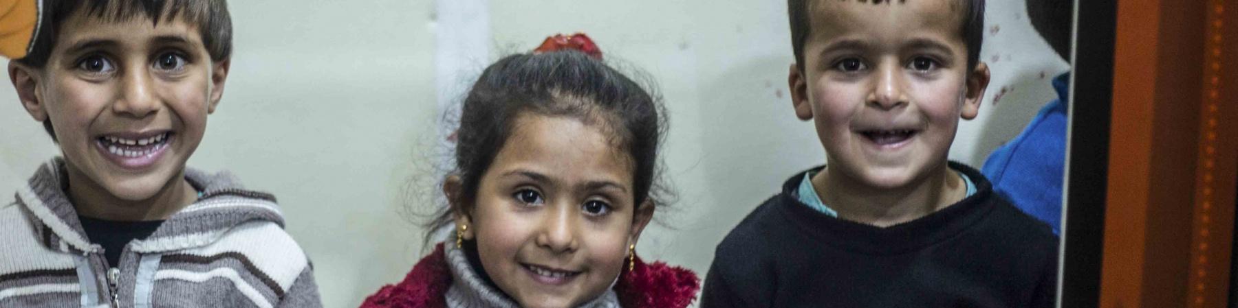 2 bambini e una bambina dietro una sagoma di cartone che simula lo schermo di un cinema