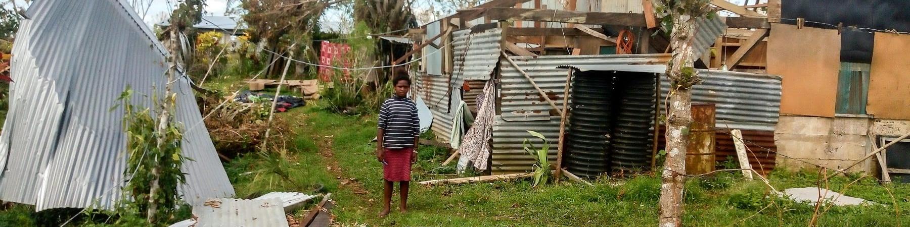 Una bambina in lontananza con gonna rossa e maglietta a righe bianche e nere si trova in piedi e scalza sul prato. Dietro di lei una casa distrutta al passaggio di un ciclone sulle isole Fiji