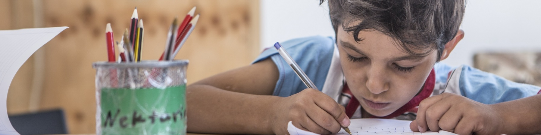 Bambino siriano fa i compiti al banco di scuola
