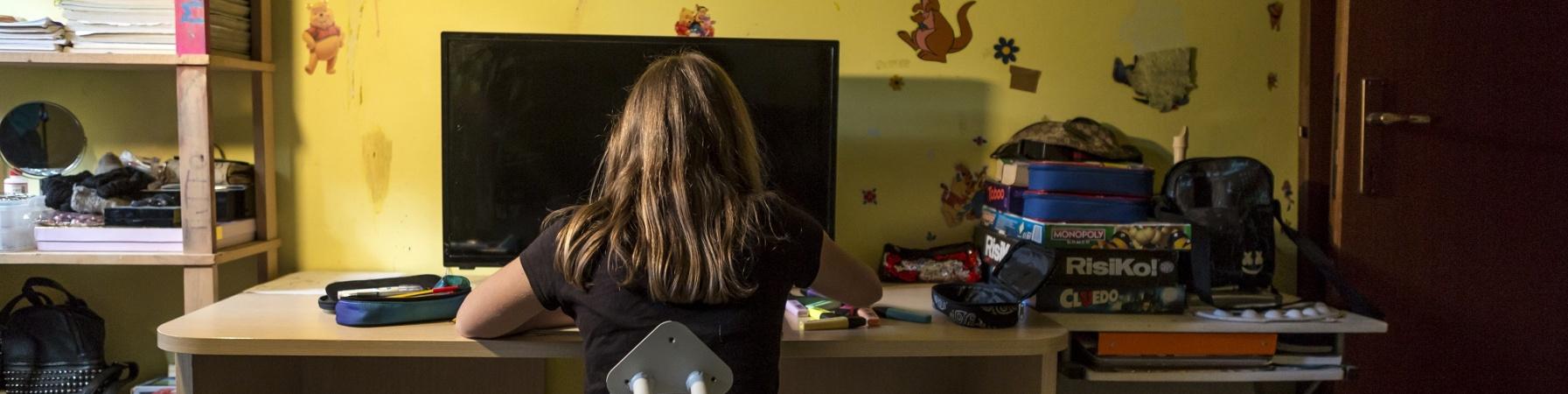 ragazza di spalle seduta alla scrivania della sua cameretta davanti al pc. Intorno a lei giochi da tavola, libri e quaderni.
