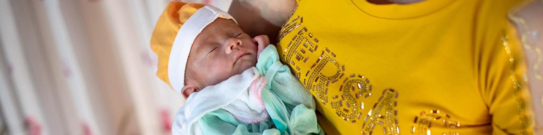 neonato con berrettino e tutina in braccio ad una donna