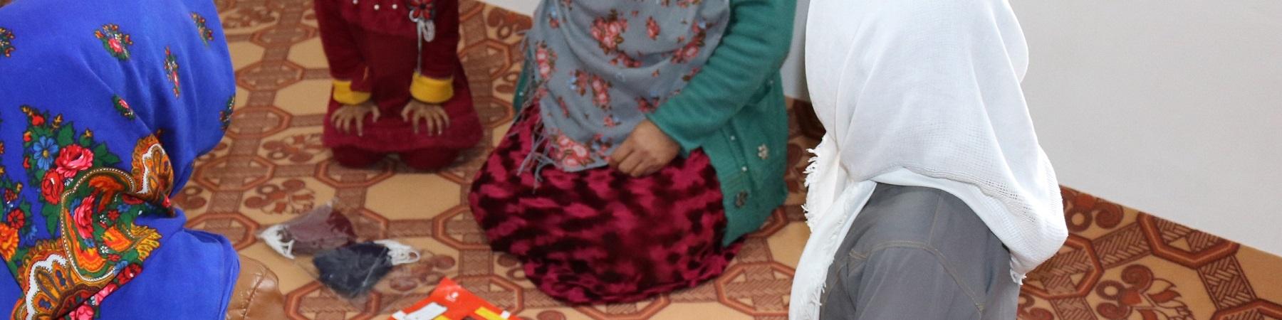 Donne di spalle riprese dall alto sono sedute a terra in circolo e indossano vestiti tradizionali afghani.