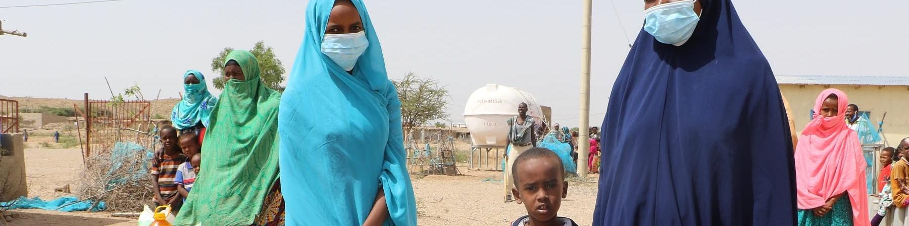 Due donne somale in primo piano e in piedi su una strada sterrata quasi desertica tengono alcune pacchi e taniche. Sono vestite integralmente di un velo, una lo porta celeste l altra blu