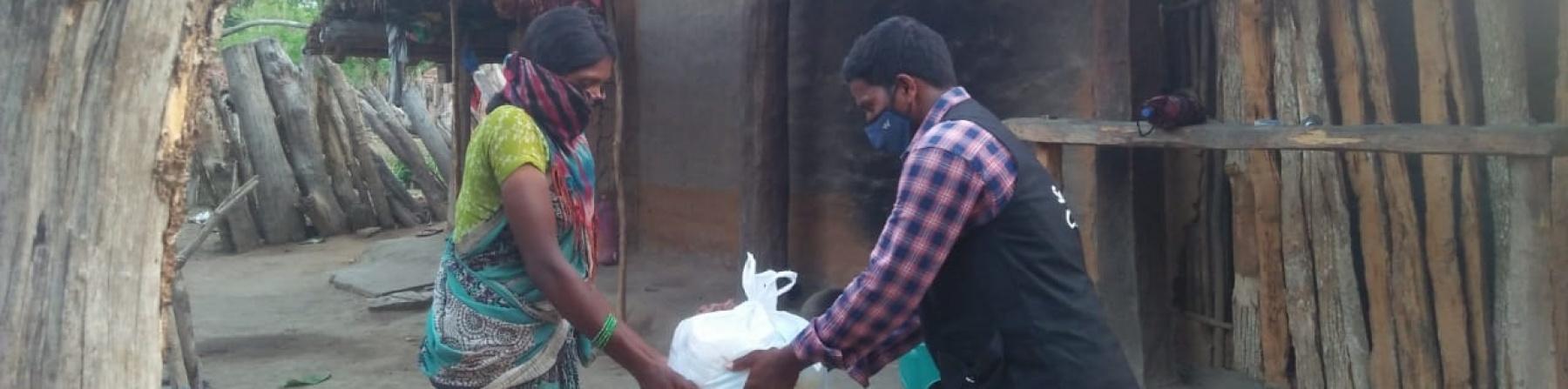 Un operatore save the children distribuisce cibo a una donna indiana, sullo sfondo una casa di legno