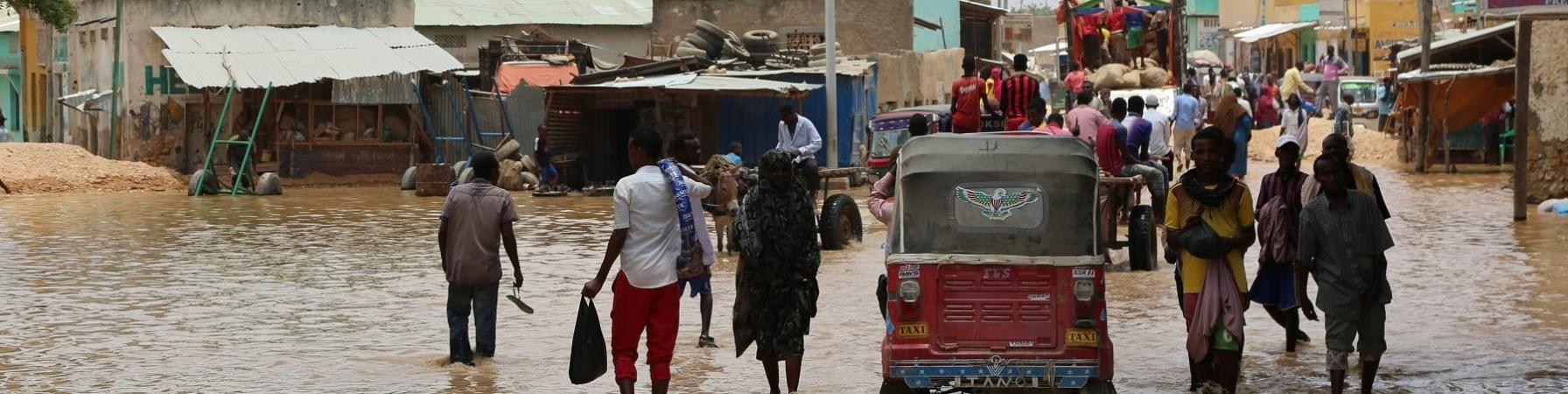 Popolazione somala sfollata a causa delle alluvioni cammina in acqua fangosa