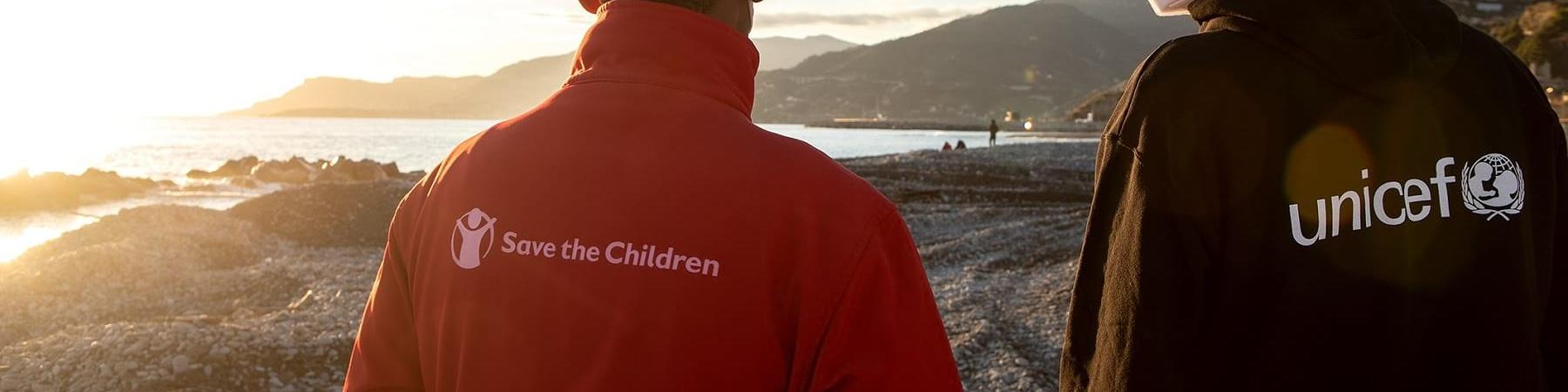 Due operatori, uno save the children e l altro Unicef, di spalle guardano un tramonto davanti a loro.