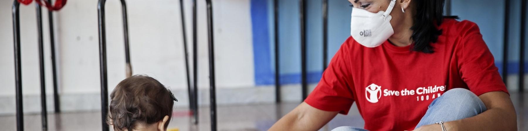 operatrice save the children con maglietta rossa con logo seduta per terra con una bimba di spalle mentre giocano insieme