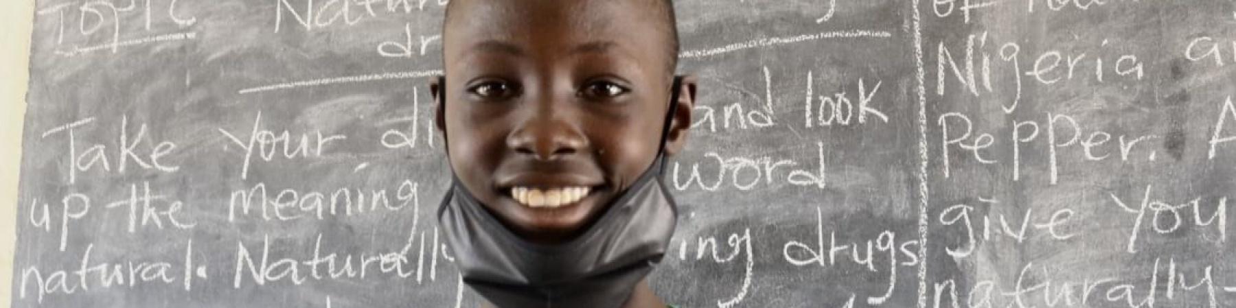 Bambino in primo piano sorridente con mascherina nera abbassata davanti a una lavagna scritta. Indossa una maglietta verde dell adidas