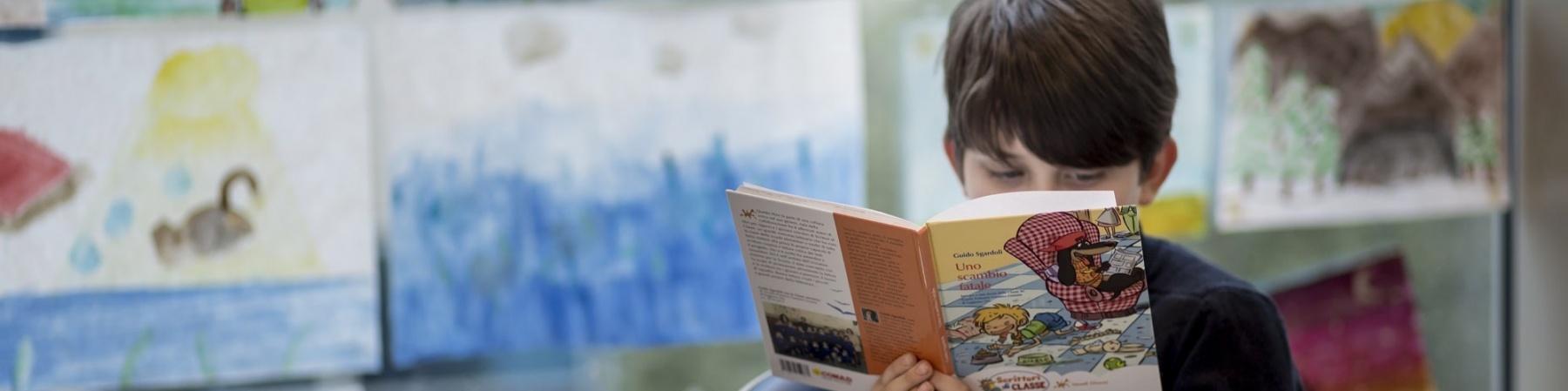 bambino seduto su una sedia davanti a un banco di scuola mentre legge un libro che tiene di fronte al suo viso