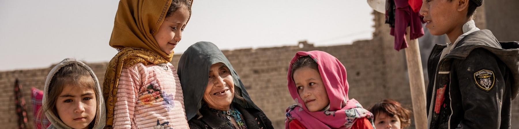 Una famiglia afghana seduta all'aperto, composta da una donna, tre bambine e un bambino.