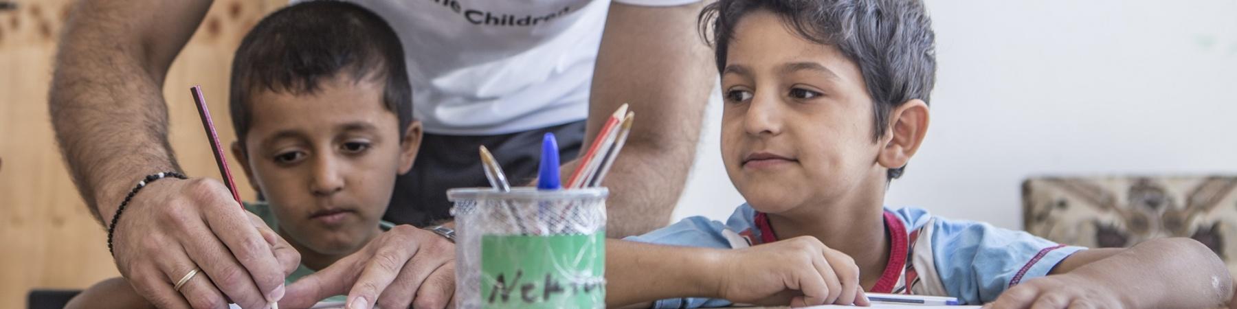 operatore umanitario in piedi aiuta due bambini seduti al banco di scuola a fare i compiti