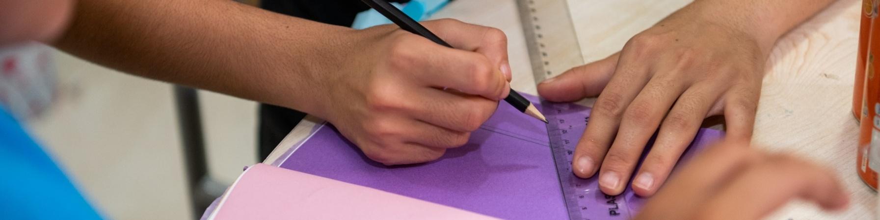 4 mani di bambini che disegnano con righello e matita su fogli
