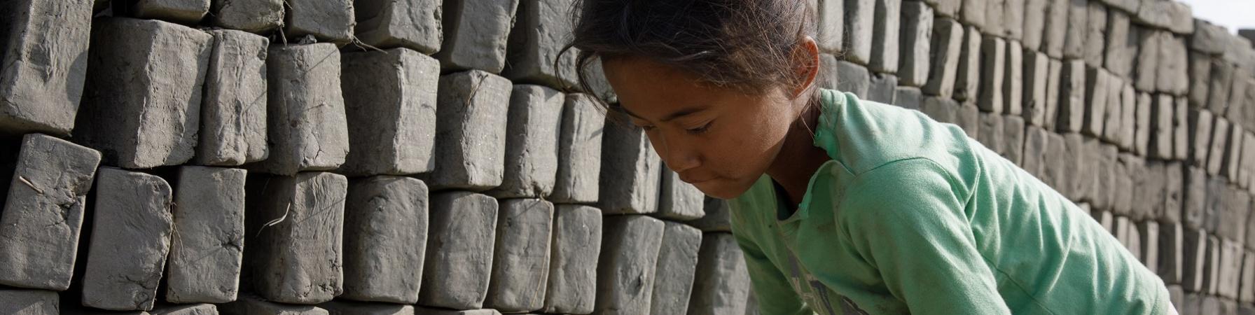 Bambina nepalese sposta mattoni in una fornace di fabbricazione