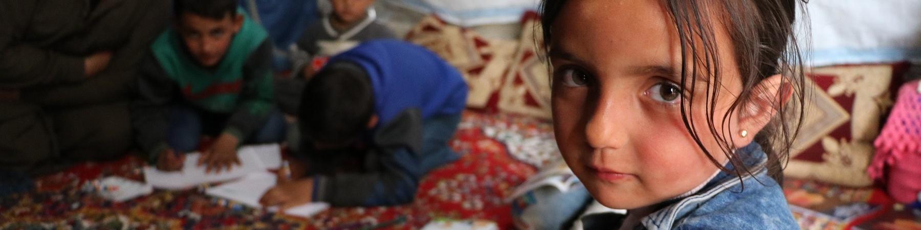 bambina seduta su un tappeto guarda in camera, sullo sfondo altri bambini