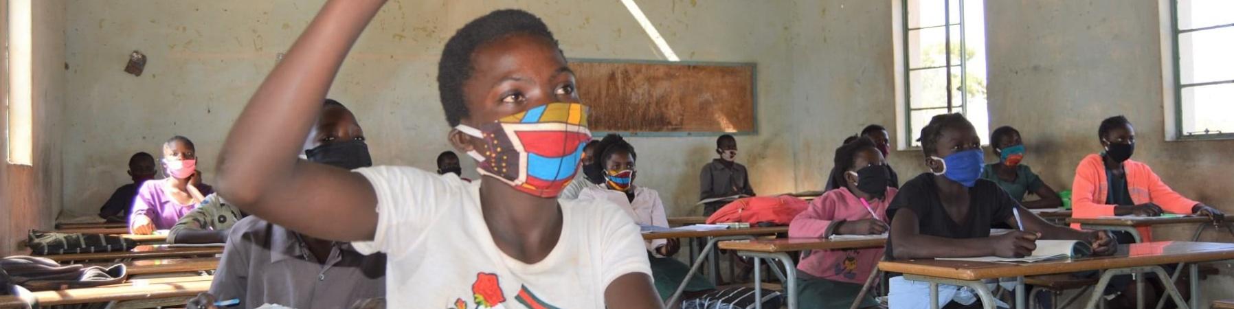 Bambina dello Zambia con la mascherina seduta al banco in classe con mano alzata