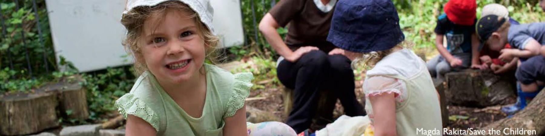 bimba sorridente in primo piano, sullo sfondo altri bambini e bambine che giocano insieme