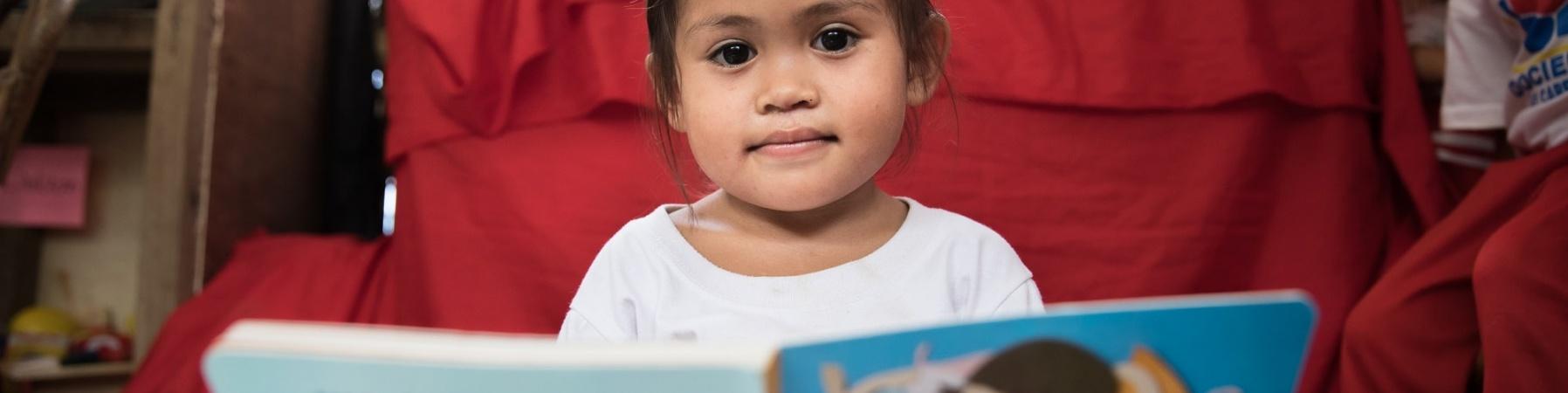 bimba del sud est asiatico con occhi scuri e capelli castani seduta con un libro grande quanto lei aperto innanzi a sè.