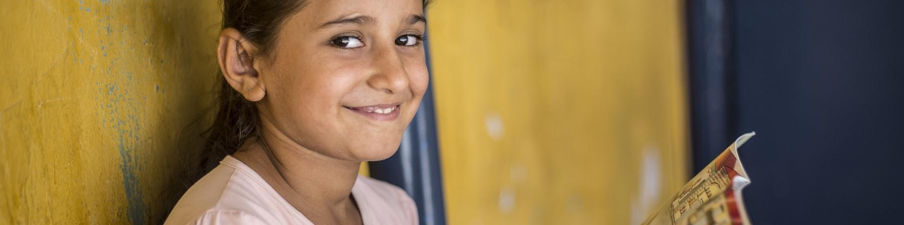 Bambina sorridente guarda in camera mentre tiene in mano un libro aperto e colorato