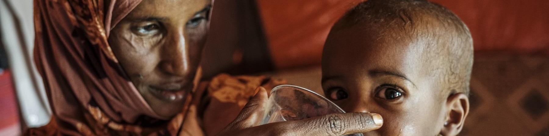 Una madre dà da mangiare a suo figlio di 5 mesi con una tazza