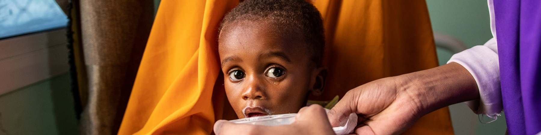 bimbo in braccio alla sua mamma mentre gli viene dato del latte da un'operatrice