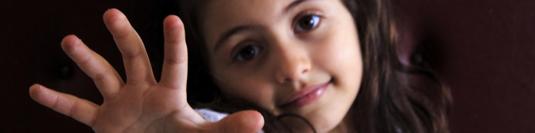 Bambina foto a mezzo busto in primo piano la mano aperta