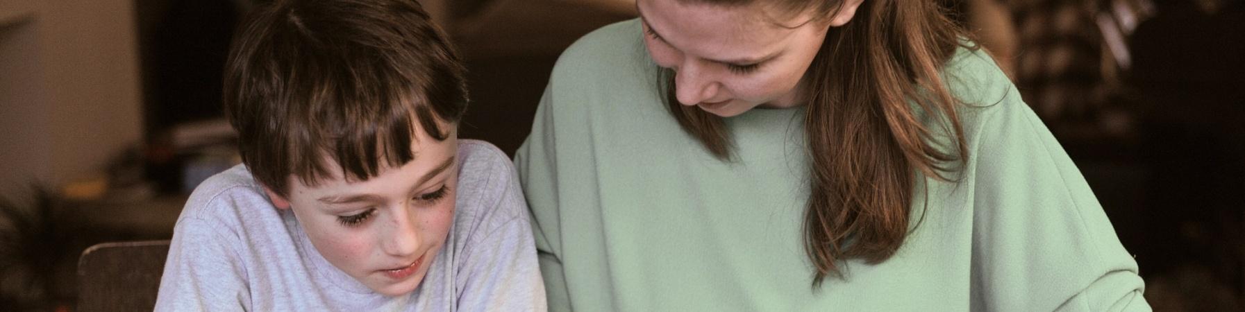 Mamma e bambino mezzo busto al tavolo che leggono