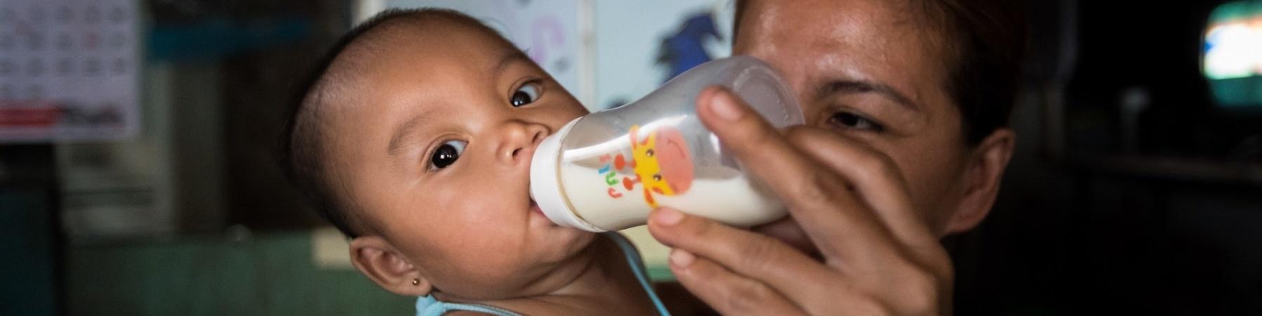 primo piano di mamma che allatta con biberon il suo piccolo figlio vestito di azzurro