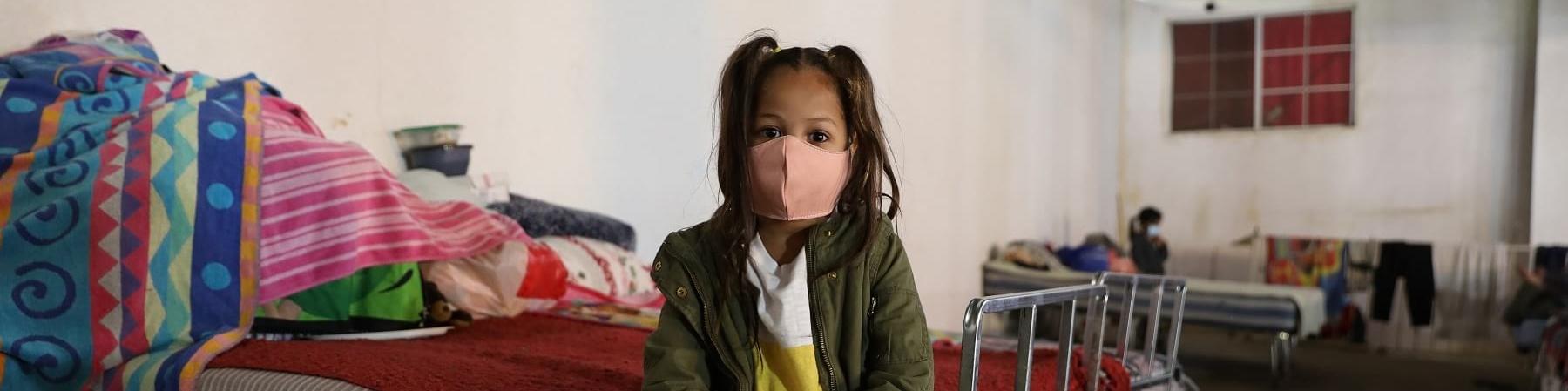 Una bambina latino-americana seduta su un letto in una stanza. La bambina ha i capelli neri legati in codini ha un maglioncino verde e e dei leggins a scacchi