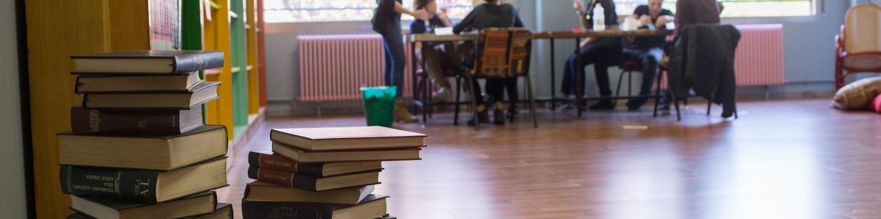 biblioteca, in primo piano dei libri accatastati e sullo sfondo delle persone intorno a un tavolo