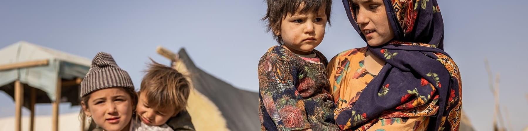 Quattro bambini afgani: una bambina tiene in braccio un bambino più piccolo, un altro bambino tiene sulle spalle un bimbo piccolo. Sullo sfondo le tende del loro villaggio