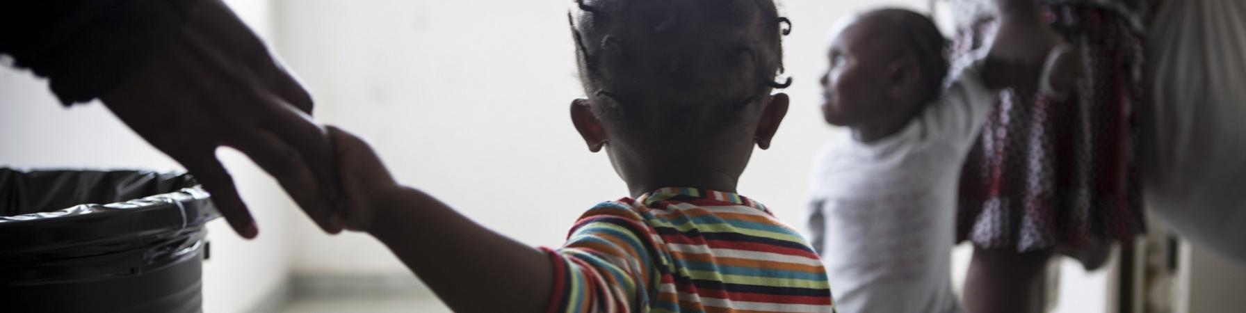 minore-migrante-di-spalle-per-mano-a-adulto