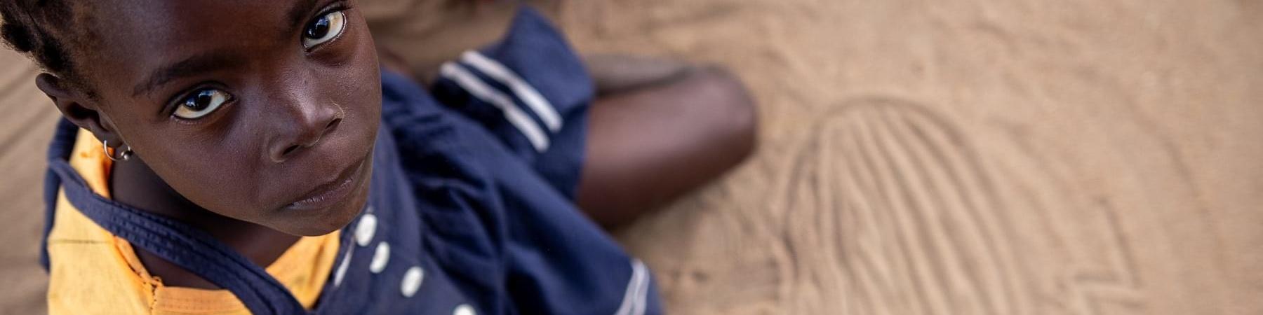 Bambina mozambicana ripresa dall alto è seduta a terra e guarda verso l alto. Indossa un vestito blu e una maglietta arancione.