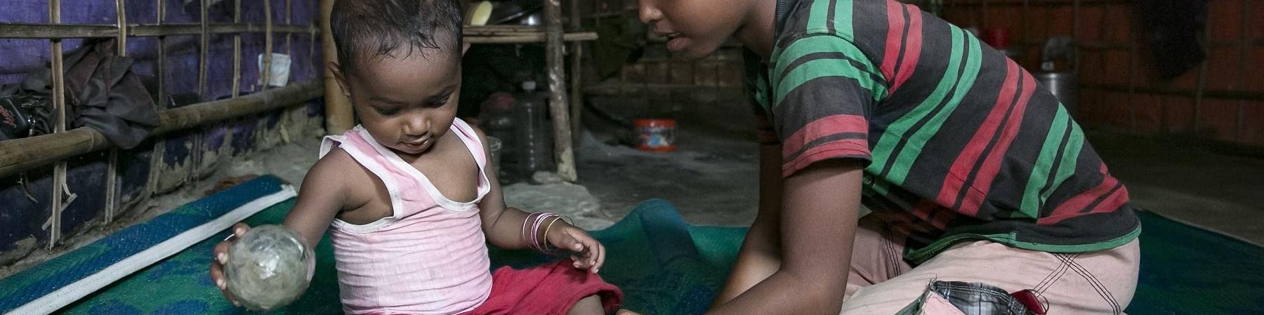 Un bambino di circa sei anni gioca seduto a terra su un tappeto verde con un bambino di circa un anno. Entrambi sono del Myanmar.