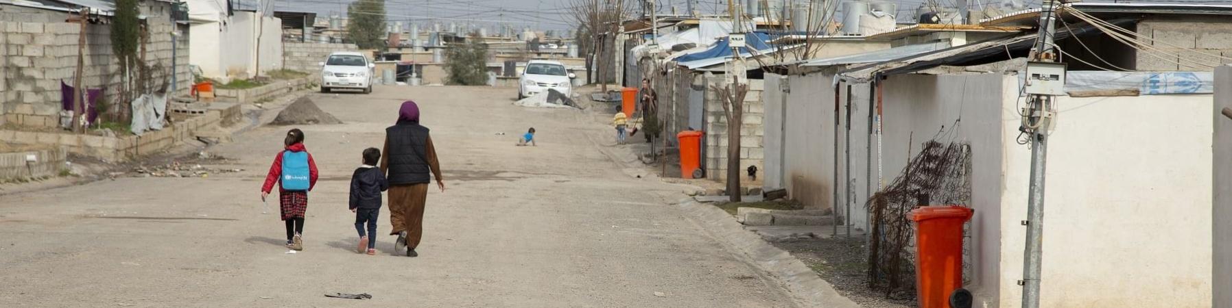 viale di un campo profughi con al centro in lontananza e di spalle tre persone che camminano